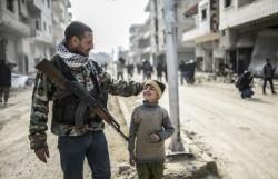 Un combattant kurde et son fils dans Kobané, libéré. Crédit photo: AFP.