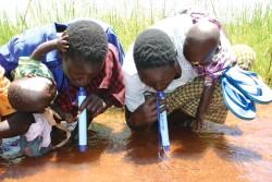 Deux personnes boivent à l'aide d'une paille filtrante, qui filtre 99,999% des bactéries et impuretés.