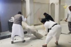 Plusieurs hommes détruisant des oeuvres du musée de Mossoul, en Irak. Source: Paris Match