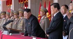 Kim Jong-Un profitant du défilé aux côtés de ses généraux et d'un représentant de la Chine.