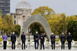 Le Secrétaire d'État John Kerry (au centre gauche) échange une accolade avec le Ministre des affaires étrangères japonais Fumio Kishida devant le mémorial d'Hiroshima. (c) J. ERNST