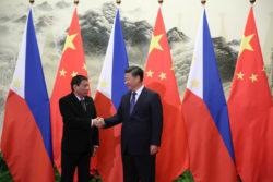 Les présidents Duterte et Xi Jinping se serrent la main.