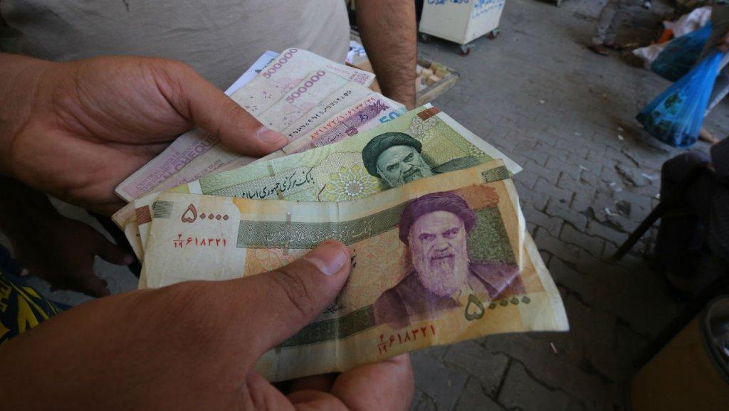 différents billets iraniens dans une main