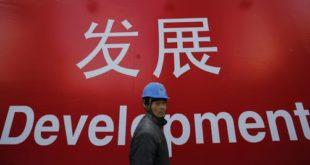 Ouvrier chinois se tenant devant une affiche du développement économique